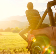 person sitting on the hood of a jeep in a meadow