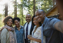 man taking selfie picture with family in front of house