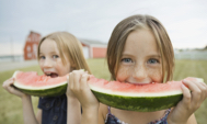 two girls eating watermelon in front of a barn